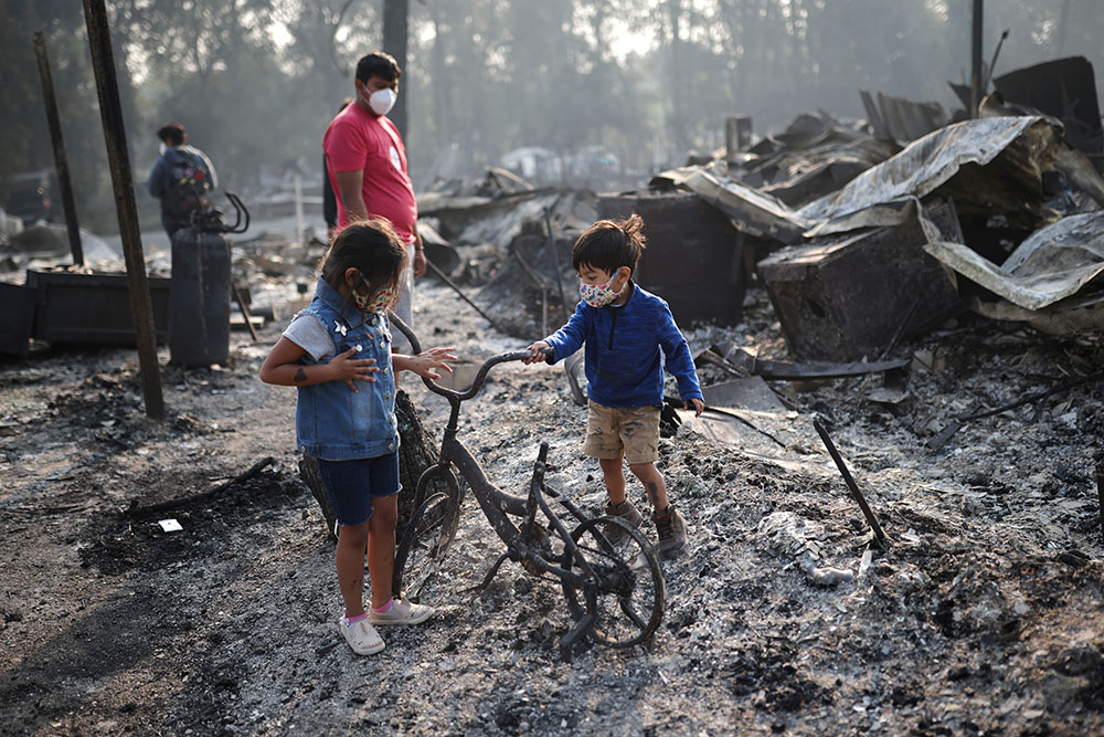 Ashley, 3, and Ethan, 2, look at a burned bicycle after wildfires destroyed a neighbourhood in Bear Creek, Phoenix, Oregon