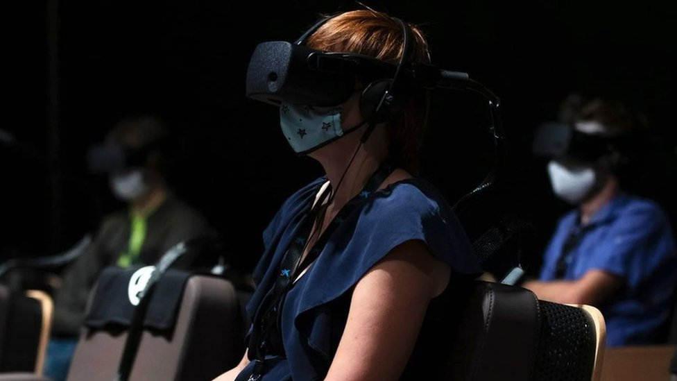 A woman at a film screening room, wearing virtual reality goggles and a protective face mask over her nose and mouth.