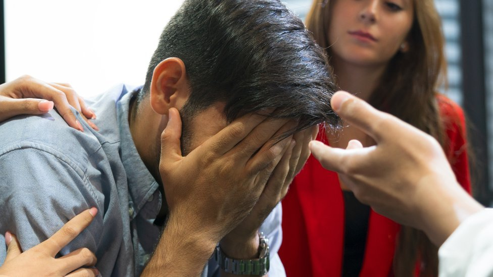 Worried man holds his head in hands