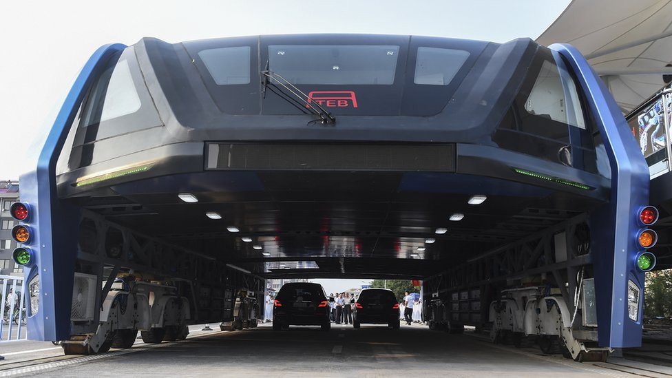 """People look at the Transit Elevated Bus TEB-1 run past vehicles as they conducted a test run in Qinhuangdao, north China""""s Hebei Province"""