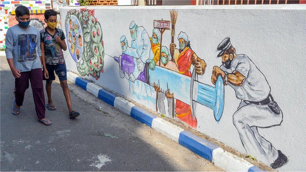 Pessoas caminhando em frente a grafite sobre covid-19
