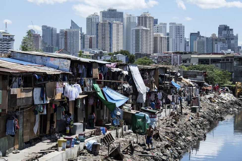 Residents of a Manila slum, pictured in front of the city's financial district