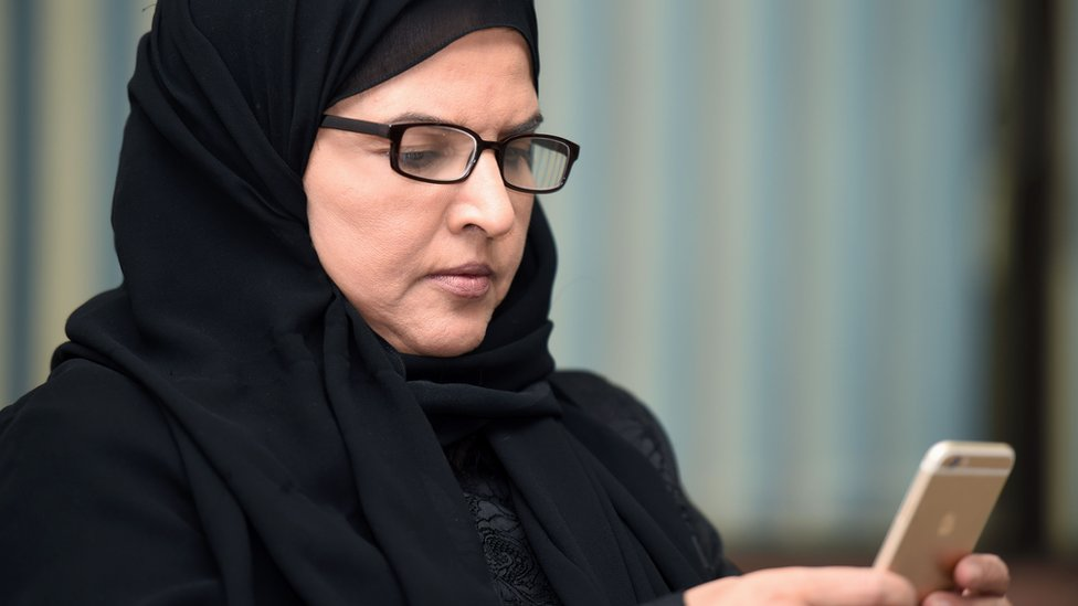 File photo showing Saudi activist Aziza al-Yousef checking her mobile phone in Riyadh on 27 September 2016