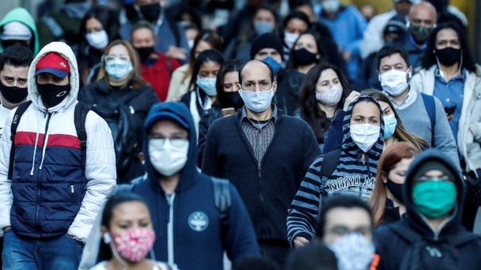 Pessoas andam na rua em São Paulo usando máscaras