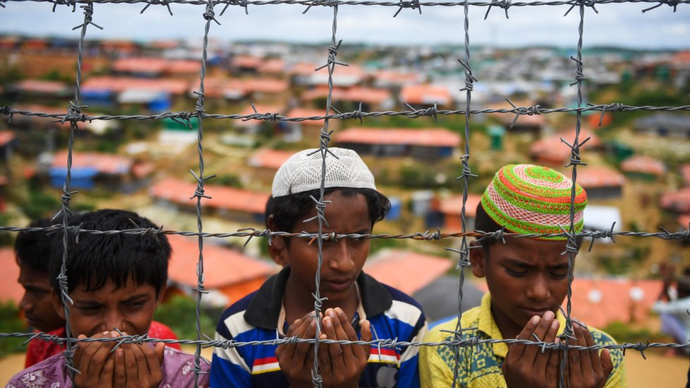 "Image of children praying behind a barbed-wire fence. In February of this year, the Bangladeshi authorities began erecting barbed-wire fences around the camps, they say, ""to prevent criminal activities"""