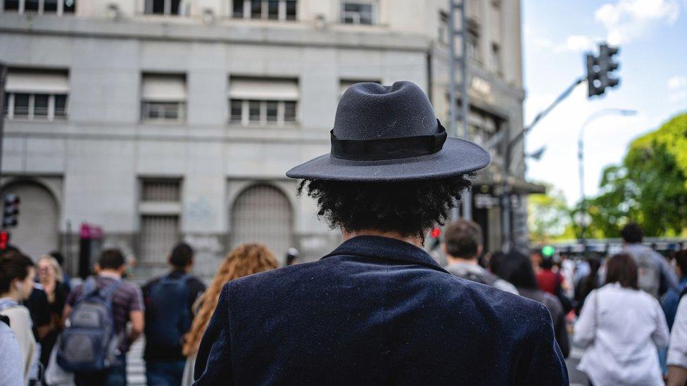 Hombre con sombrero cruza la calle.