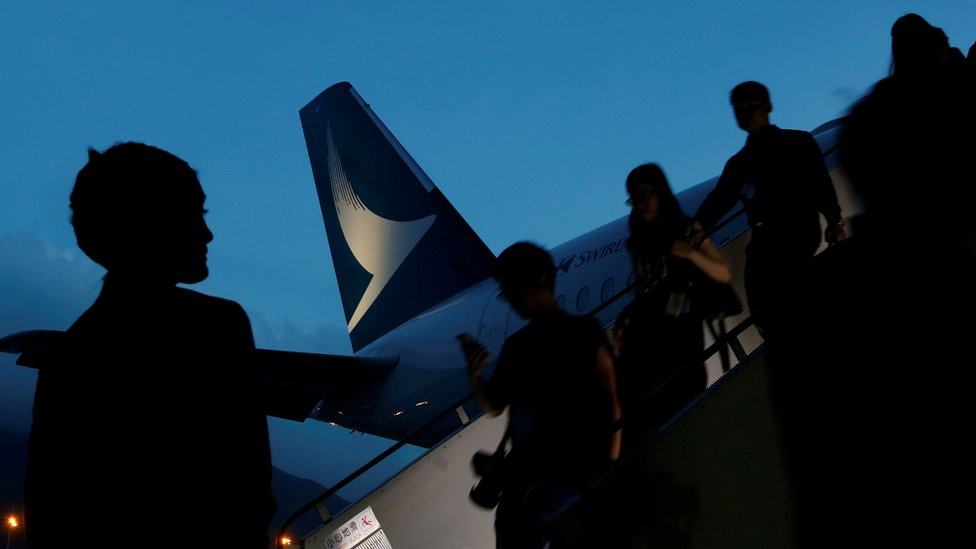 Passengers descending from a Cathay Pacific plane at night