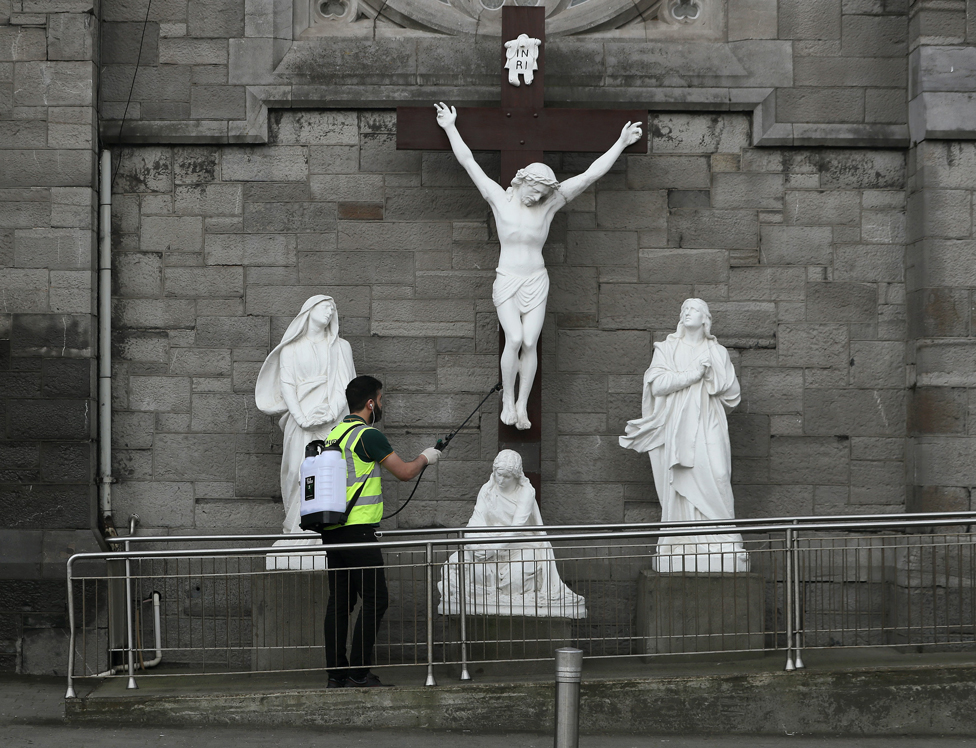A man spraying disinfectant at a statue of the crucifixion of Jesus in Dublin on Good Friday
