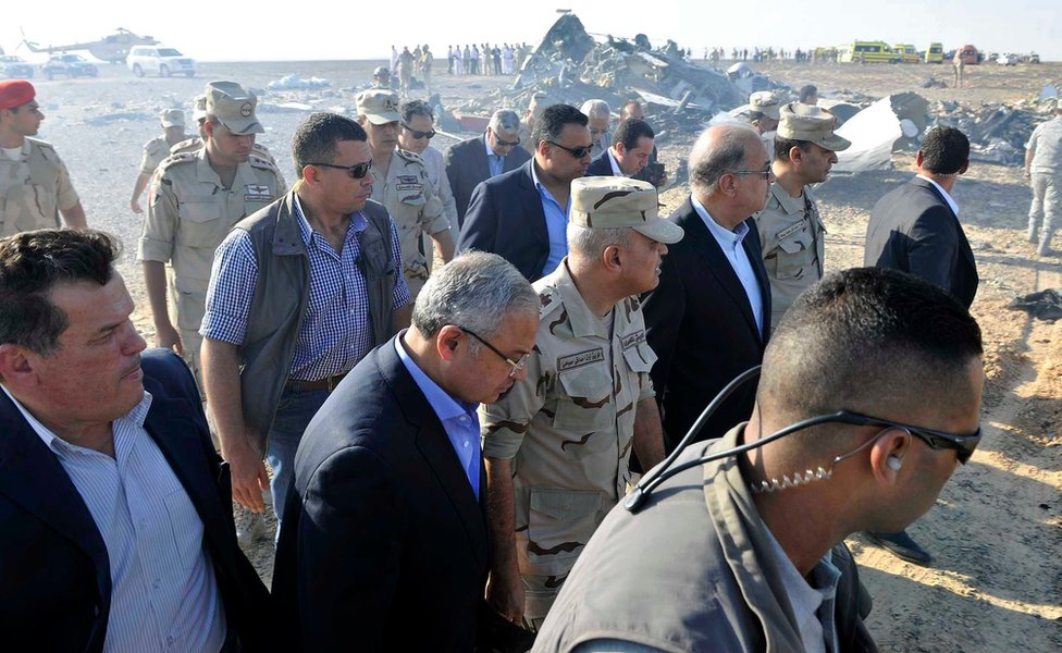 """In this image released by the Prime Minister""""s office, Sherif Ismail, third right, along with milirary and government officials, tour the site where a passenger plane crashed in Hassana Egypt, Friday, Oct. 31, 2015."""