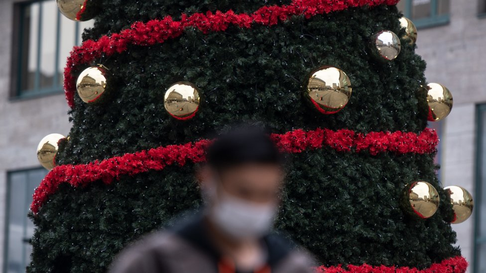 A masked man walks past a Christmas tree