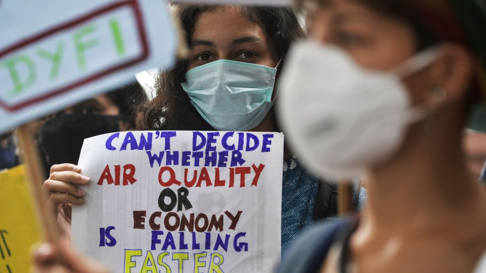 """A protester holding a sign that says: """"Can't decide whether air quality or economy is falling faster"""""""