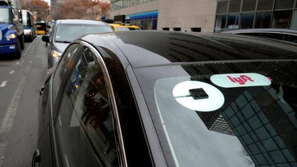 Un auto con logos de Uber y Lyft