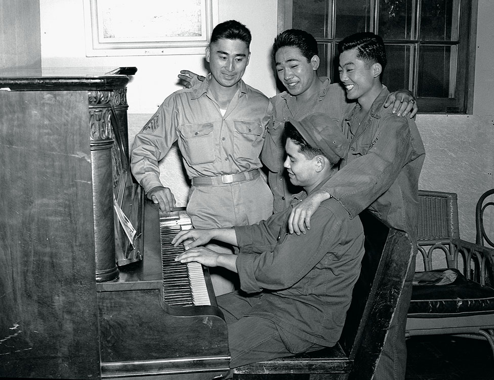 A soldier plays an piano as soldiers sing along