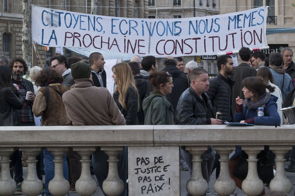 """People gather next to a banner which reads """"citizens, let's write ourselves the next constitution"""" on the Place de la Republique, in Paris"""