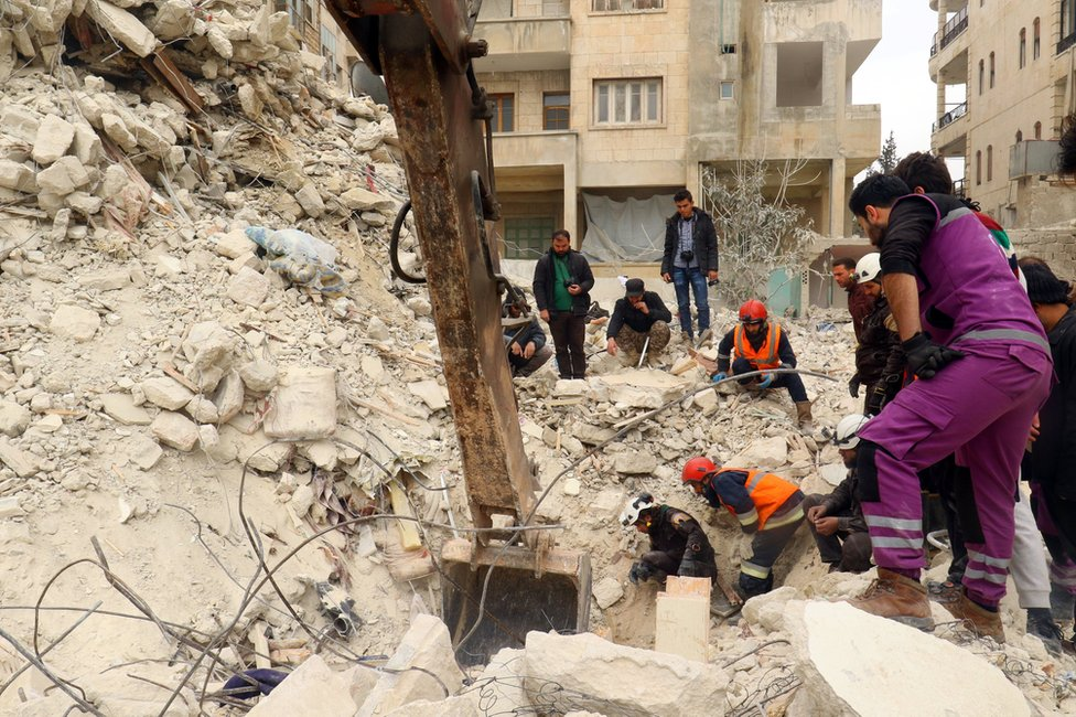 Rescue workers and civilians remove rubble from a collapsed building after a reported air strike on Idlib, Syria (15 March 2017)