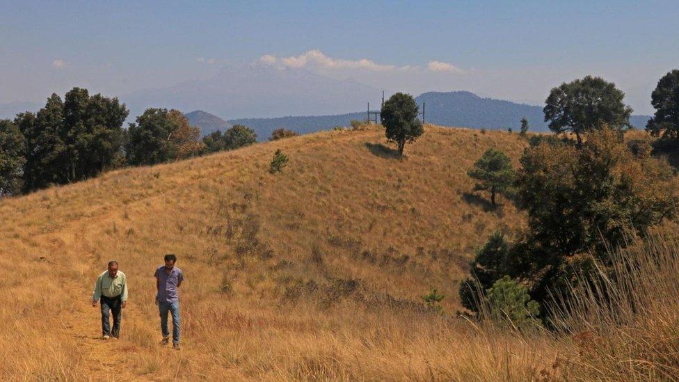 Dos hombres paseando por una colina en Milpa Alta.