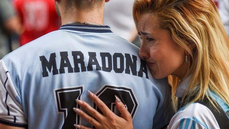 Una chica llora en el hombro de un hombre de espaldas con una camiseta con el nombre de Maradona