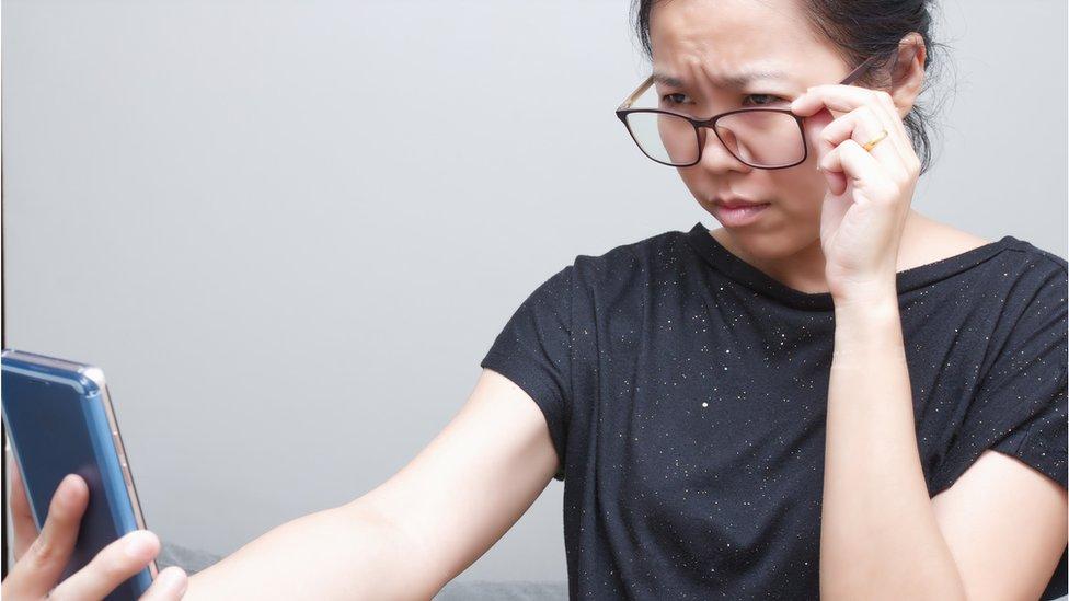 Una mujer frunce el ceño intentando leer la pantalla del teléfono celular.
