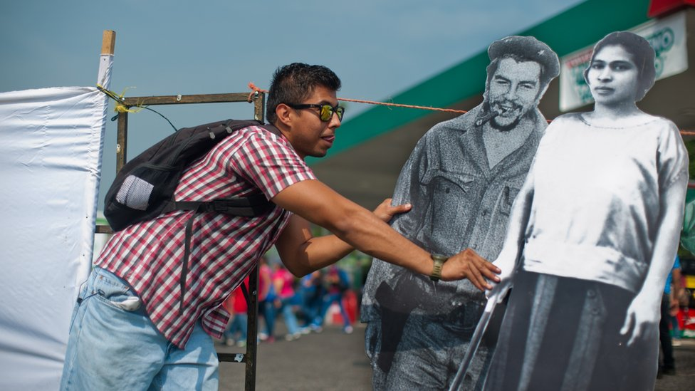 Un joven sostiene imágenes de Prudencia Ayala junto a la de Ernesto 'Che' Guevara.