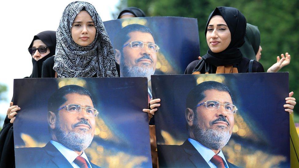 متظاهرون يحملون صور مرسي