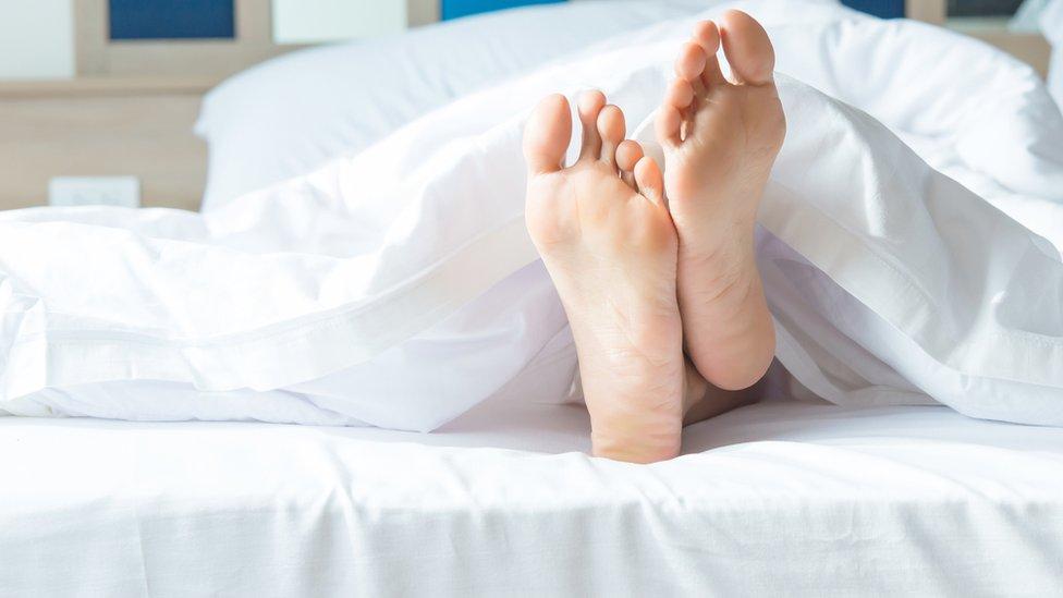 Persona durmiendo con los pies descubiertos.