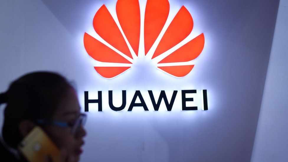A woman uses her mobile phone in front of a LED display board of Huawei at Beijing International Consumer Electronics Expo in Beijing on July 9, 2018.