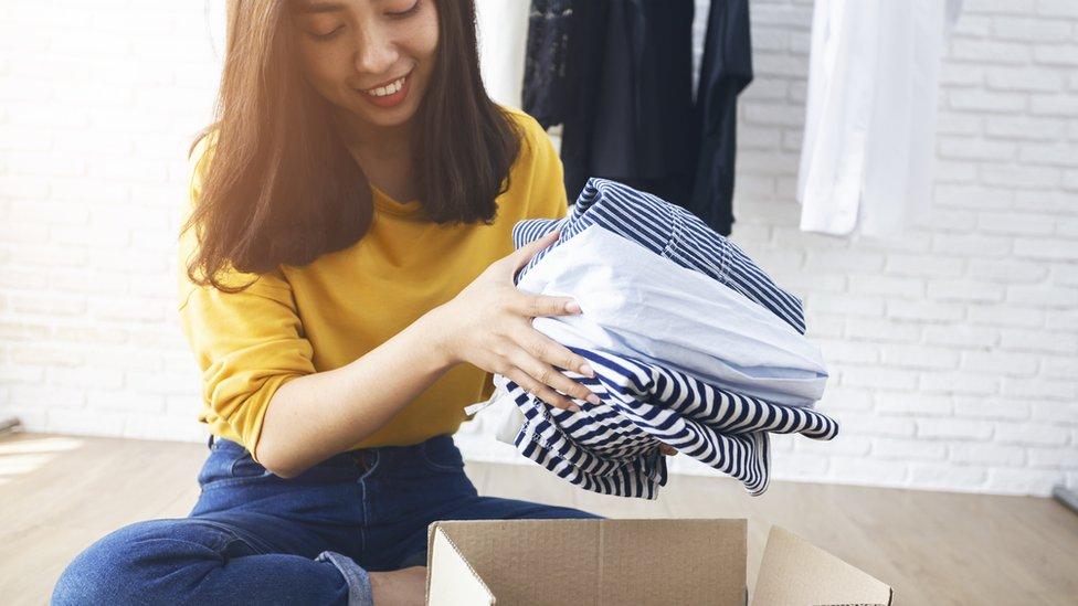 chica guardando ropa en cajas