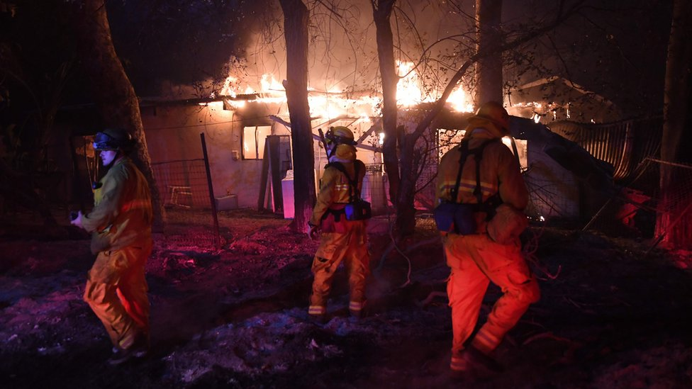 Firefighters investigate a burning house, as the Thomas wildfire continues to burn in Carpinteria, California, 10 December 2017
