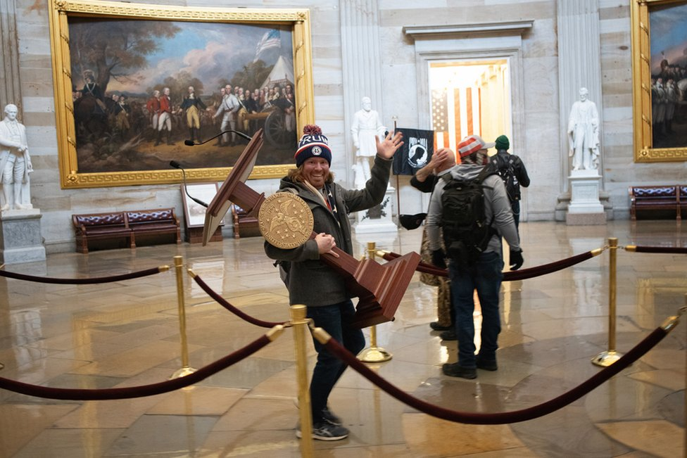 A pro-Trump protester carries the plinth of US Speaker of the House Nancy Pelosi through the Rotunda of the US Capitol Building after a pro-Trump mob stormed the building on 6 January 2021 in Washington, DC.