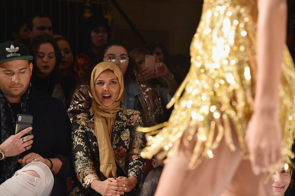 Halima Aden watching a model wearing Sherri Hill designs