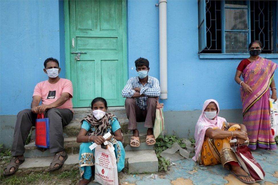 Dois homens e três mulheres com trajes típicos e máscaras na Índia, na frente de uma casa