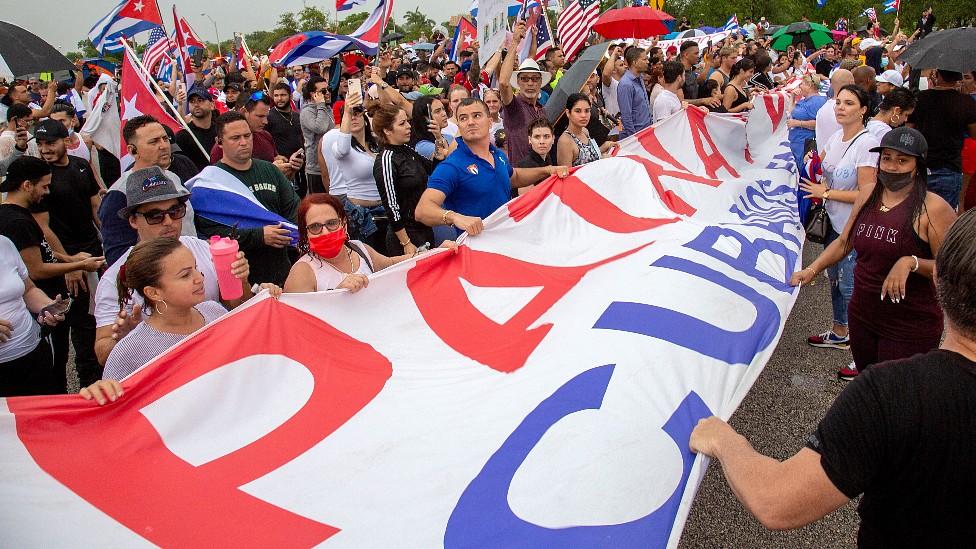 """Manifestantes en la autopista Palmetto con banderas de Cuba y una pancarta en la que se lee """"Patria y Vida"""""""