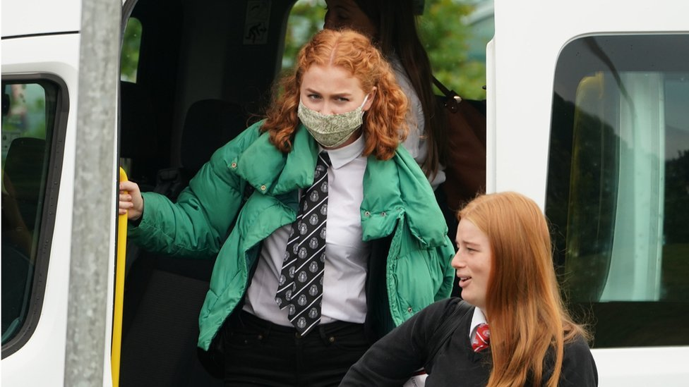 A pupil wears a face covering getting off a school bus in Scotland