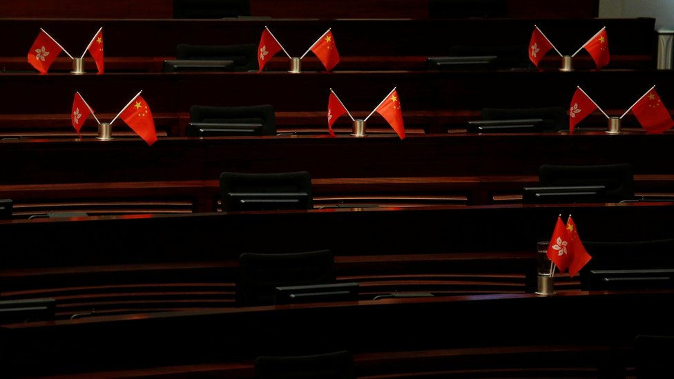 Empty seats with China and Hong Kong flags are seen inside a chamber after pro-Beijing lawmakers staged a walk-out