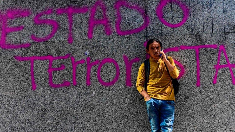 """Una pintada en una pared dice """"Estado Terrorista"""""""