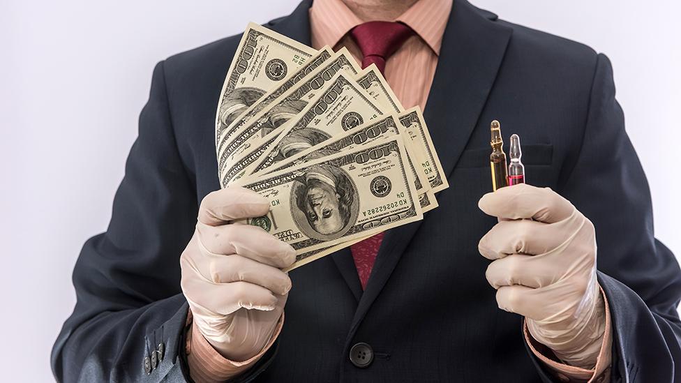 Un hombre con guantes de latex, sosteniendo vacunas en una mano y dinero en la otra