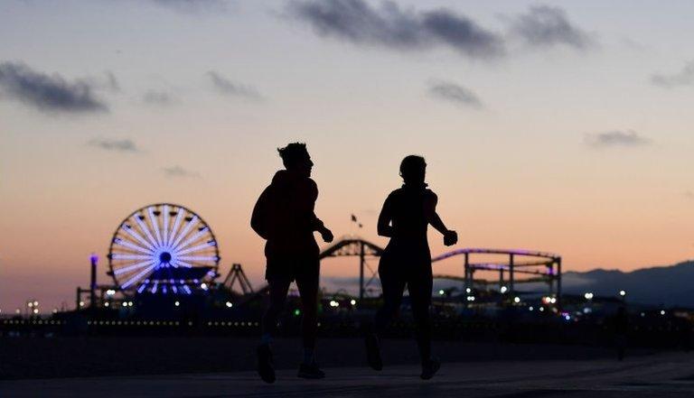 Pessoas correm no calçadão da praia em Santa Monica, na Califórnia