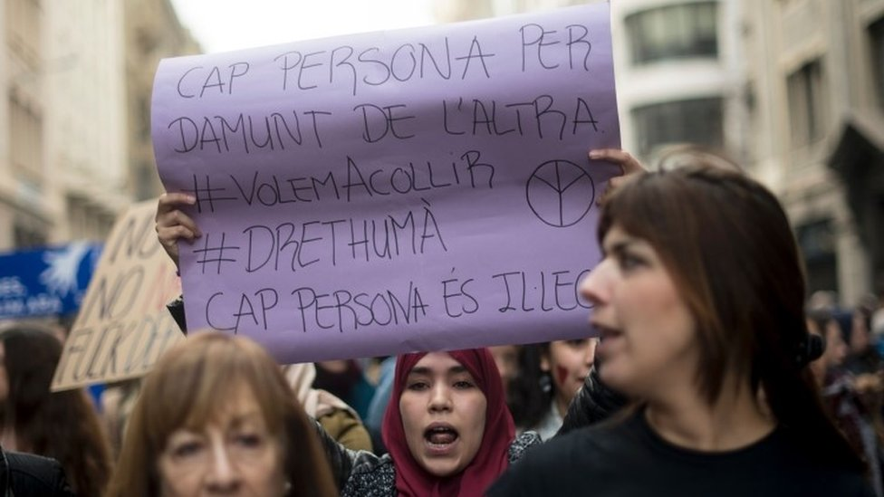 """A woman holds a placard reading """"No one is above another, No one is illegal"""" during Saturday's demonstration (18 February 2017)"""