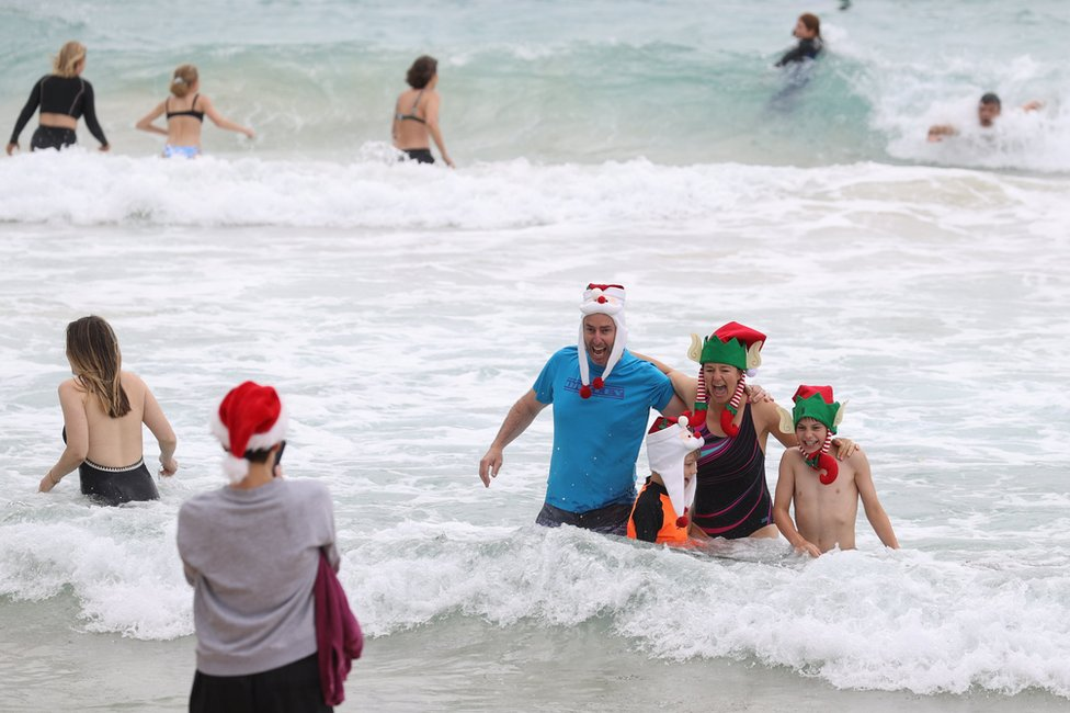 People wear Christmas-themed attire at Bondi Beach in Sydney, Australia. Photo: 25 December 2020