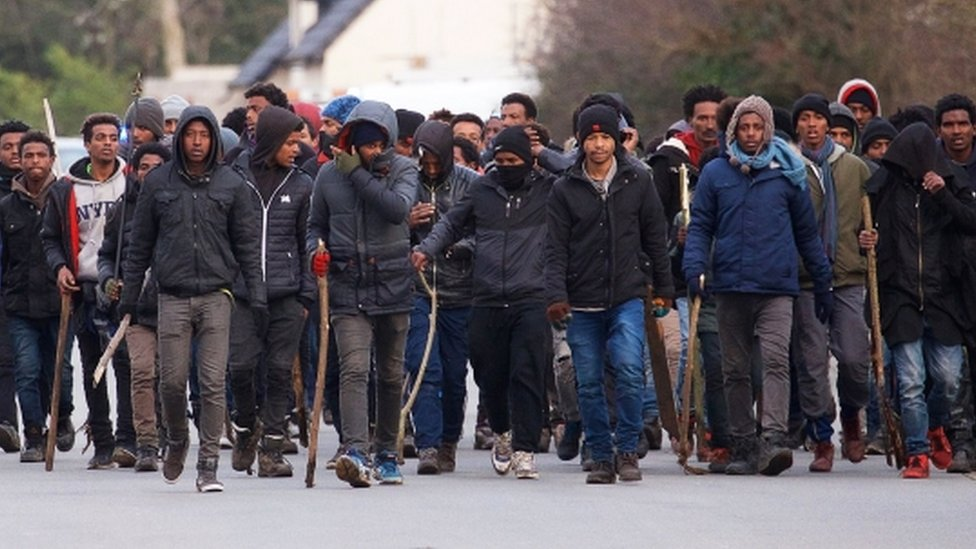 A group of migrants carry sticks during clashes in Calais on 1 February 2018.