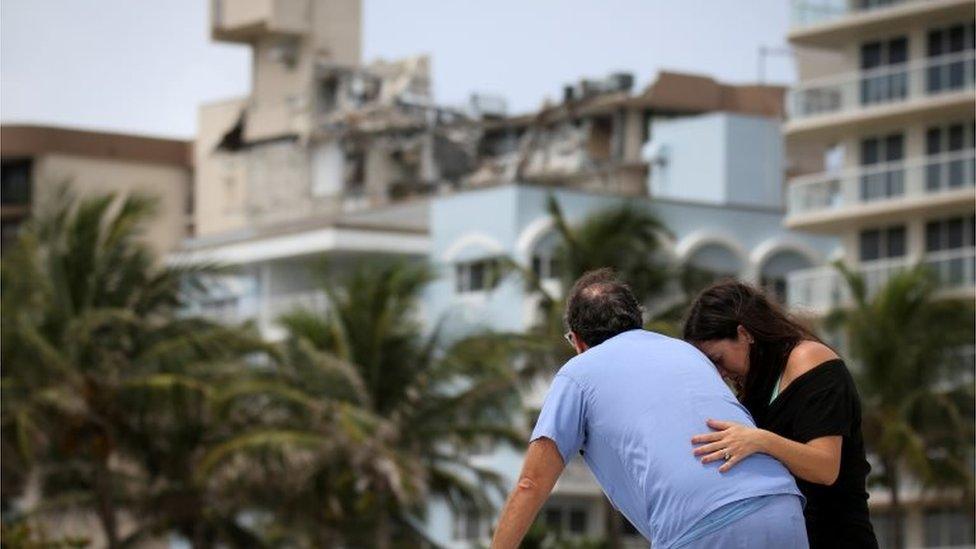 Dos personas frente a la torre colapsada