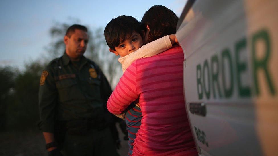 Una mujer sostiene a un niño ante un agente fronterizo