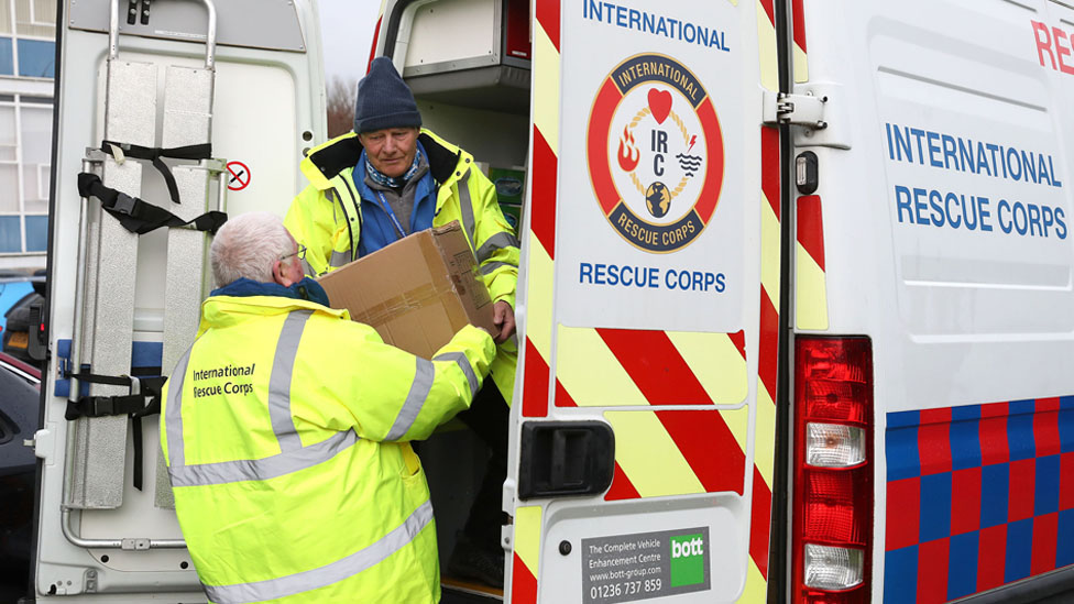 Members of International Rescue Corps load supplies into vans at Camelon community centre
