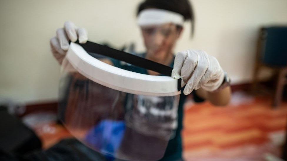 A medical student checks a handmade face shield before delivering them to doctors and nurses in Yangon, Myanmar.