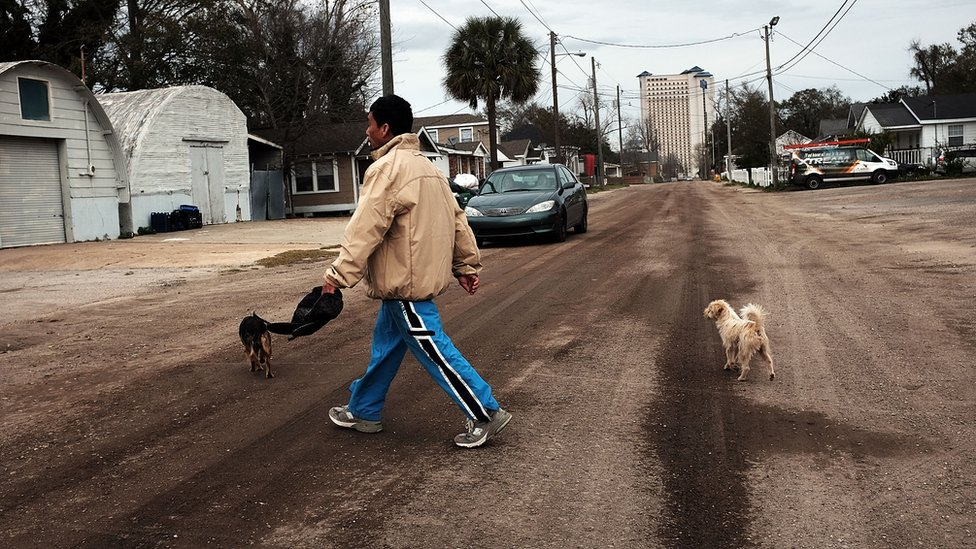 Hombre cruza una calle en Biloxi, Misisipi.