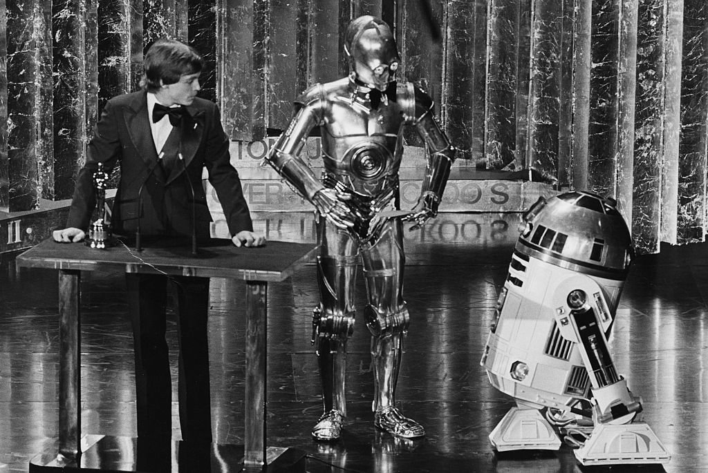 Actor Mark Hamill presenting an award with his Star Wars co-stars C3PO and R2D2 at the 1978 Oscars