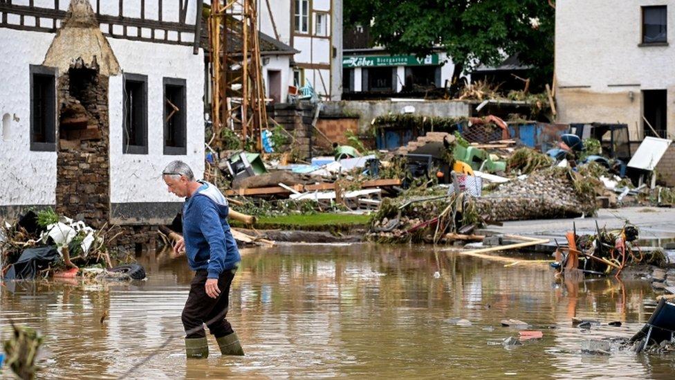 Un hombre camina a través de las inundaciones en Schuld, Alemania.