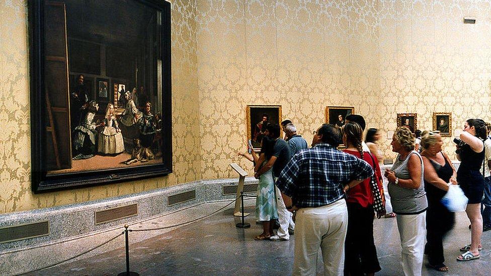 """Visitantes mirando """"Las Meninas"""" en el Museo del Prado."""