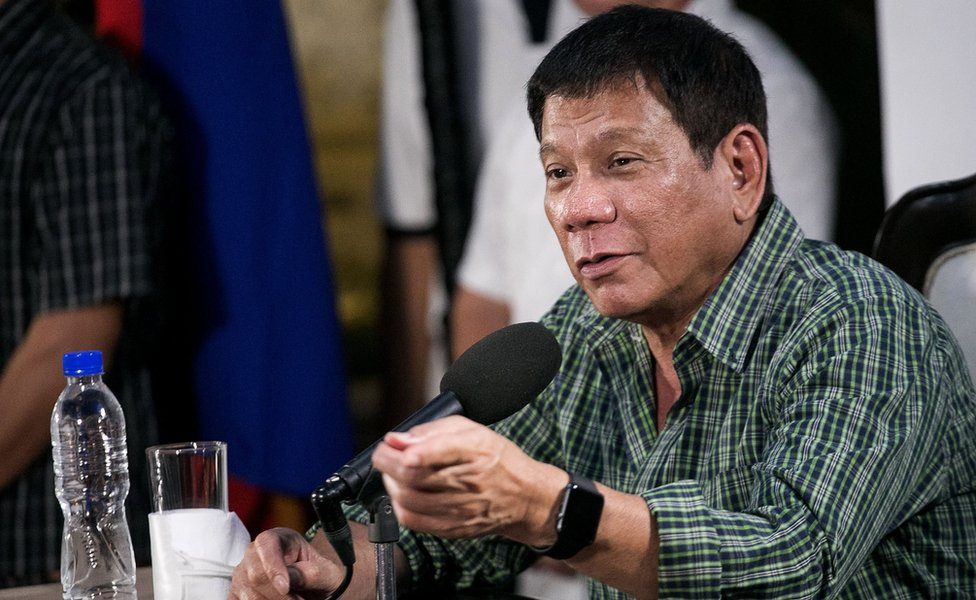 Rodrigo Duterte speaks during his press conference, seated at a microphone and wearing an open-necked check shirt, on 31 May 2016.