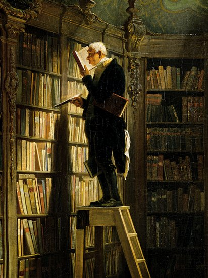 Bibliófilo mirando su colección.